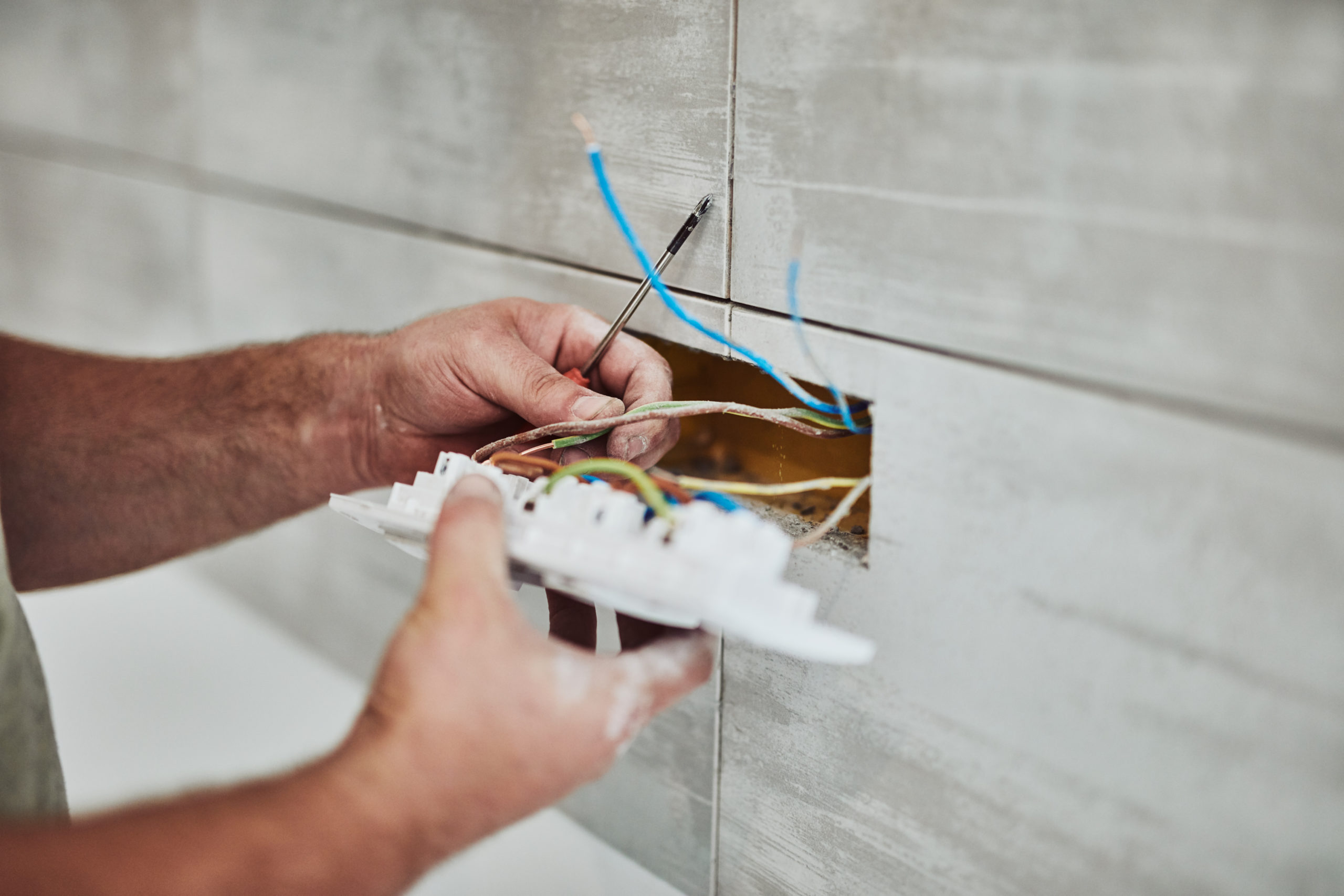 Electrician repairing / fixing wires in the wall.